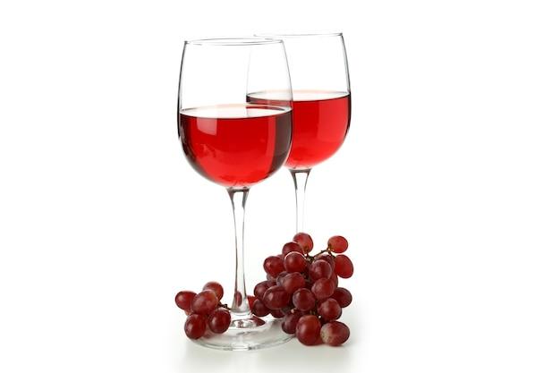白地に分離された赤ワインとブドウのグラス
