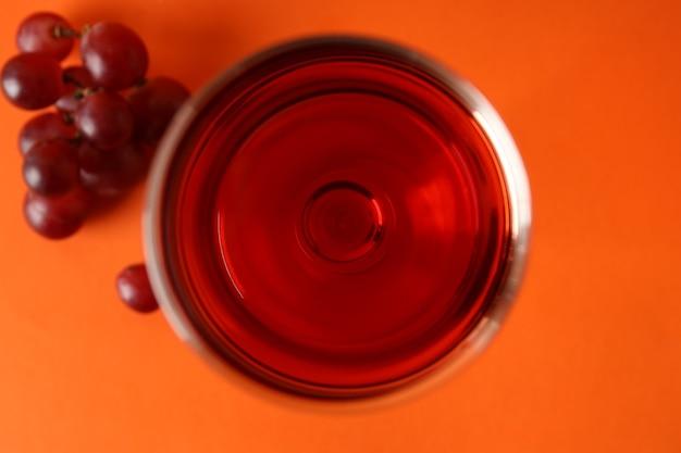 オレンジ色の背景に赤ワインとブドウのグラス
