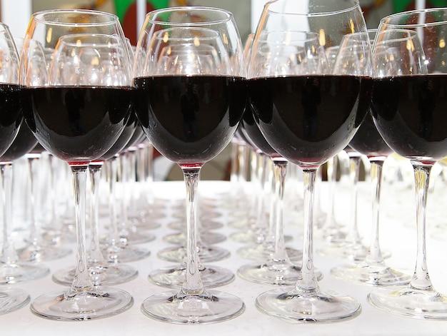 白いテーブルのクローズアップに赤ワインのグラス