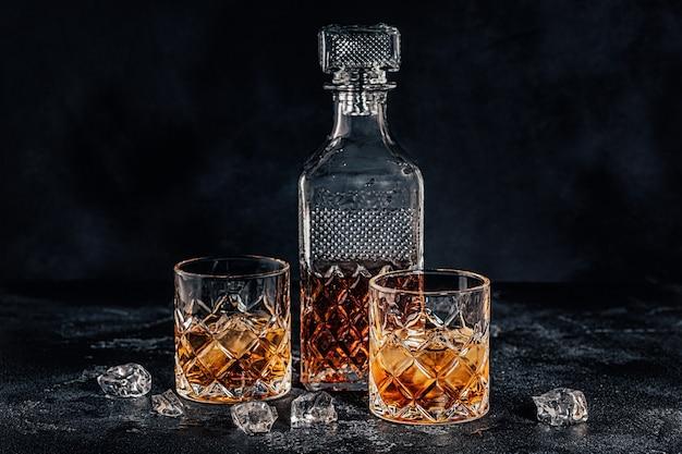 黒い石の背景に正方形のデカンターとウイスキーのグラス。