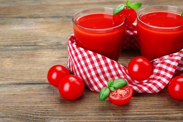 Стаканы томатного сока с овощами на деревянных фоне