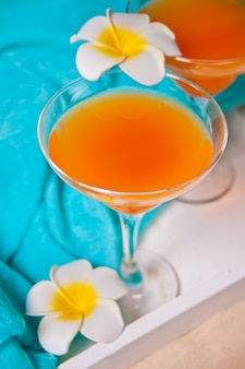 Очки тропического экзотического мультифруктового сока коктейль пьют на белом подносе с цветком франжипани plumeria. концепция пикника на пляже.