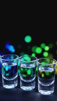 ウォッカまたはテキーラのグラス。バーで-ネオンの背景