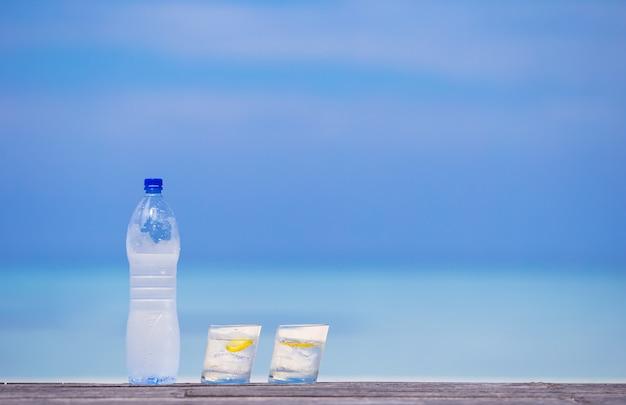 海の背景に木製のボトルにレモンと水のグラス