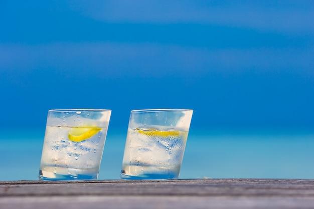 海の背景に木製のレモンと水のグラス