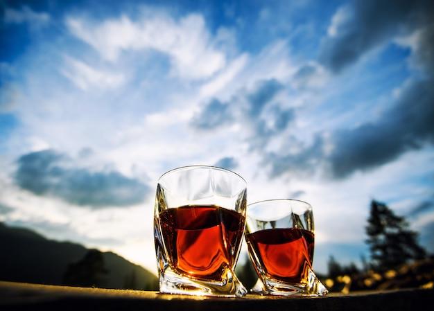山の風景の背景にウイスキーのグラス