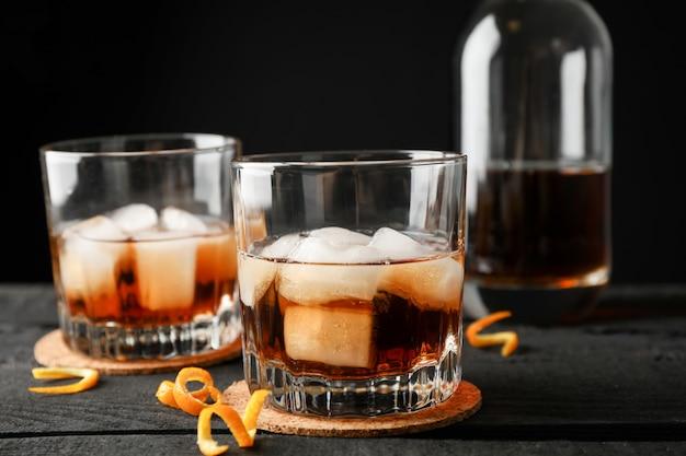 ウイスキーとオレンジの皮、ボトルと木製の背景に氷のグラスをクローズアップ