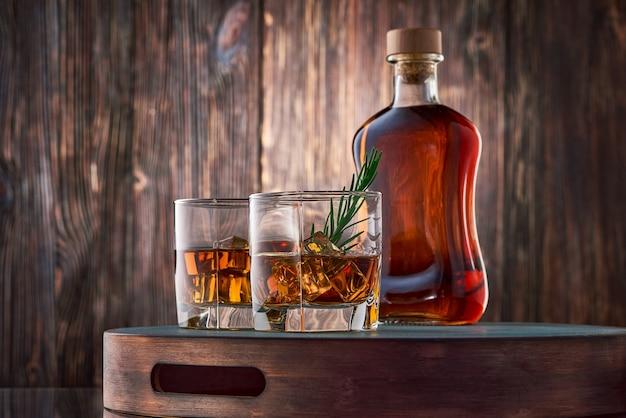 ウイスキーのグラスと木製のテーブルの上の瓶