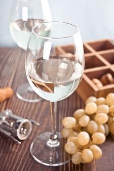 背景にブドウと木製の箱と白ブドウワインのグラス。上面図。