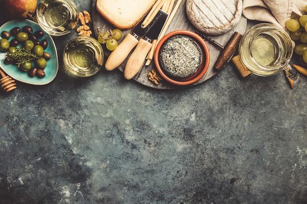 Бокалы белого игристого вина с сыром, виноградом, орехами, оливой