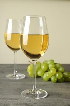 灰色のテクスチャテーブルに白ワインとブドウのグラス
