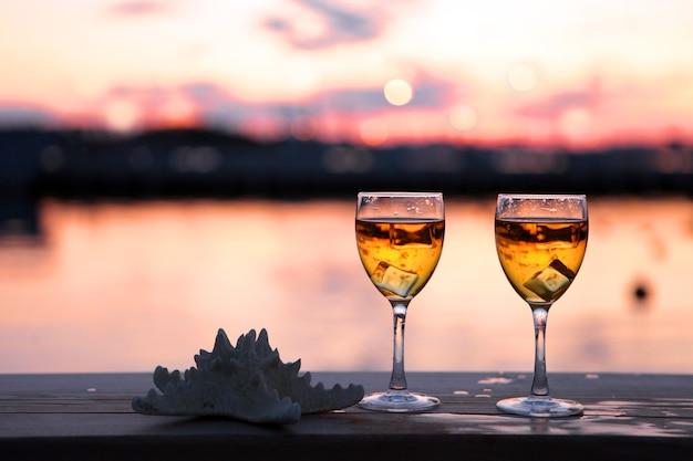 ヨットの港の赤い夕日に対して白ワインの角氷のグラス。夏の夕方の海。休暇