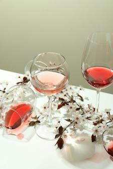 Бокалы вина и цветов вишни на белом столе