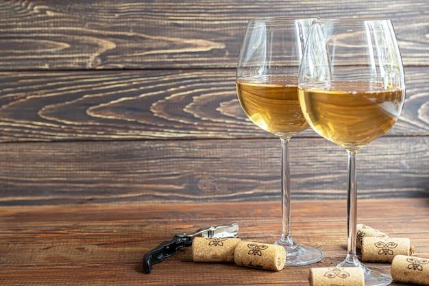 Бокалы вина и штопор на деревянном столе