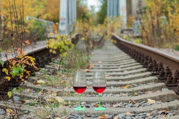 철도 트랙에서 와인 잔입니다. 알코올이 있는 오래된 빈티지 배경 트랙 레일이 사라집니다. 숲이나 숲을 통과하는 철도 단일 트랙. 여행 개념입니다. 사이트 복사 공간