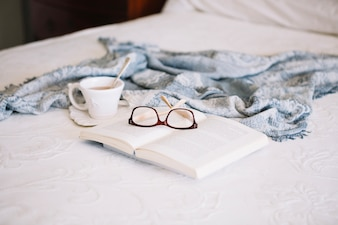 Glasses on book near cup with beverage