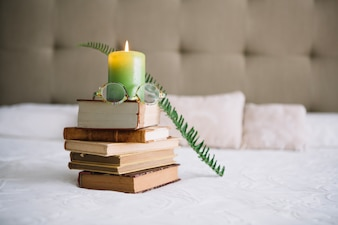 Glasses on books near candle and fern