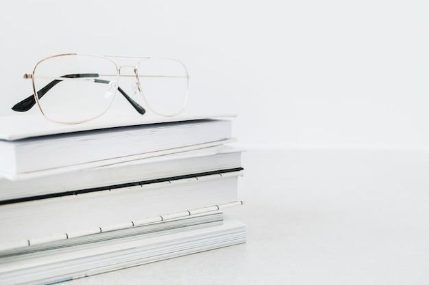 本の上の眼鏡は積み重ねます。ミニマリストのビジネスヒーローヘッダー。