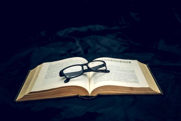 Очки на старой книге, лежащие на открытой странице старой книги