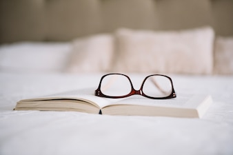 Glasses on opened book on bed
