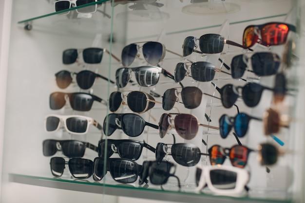 Очки на прилавке в магазине оптики. очки солнцезащитные очки в магазине.