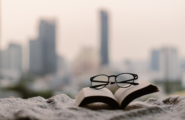 Glasses on an open book over a blanket with city background.
