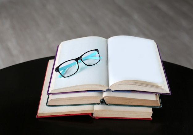 Glasses on open book on wooden table.