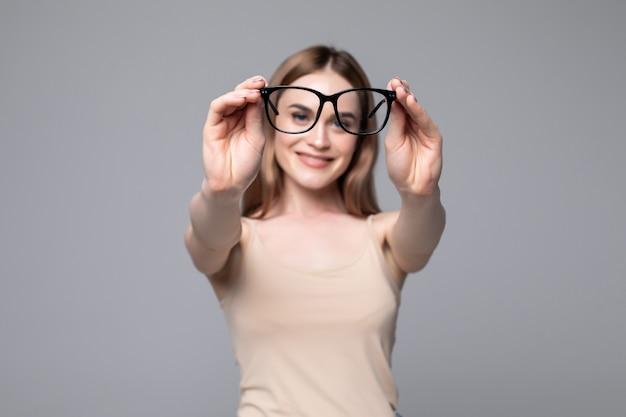 Occhiali - ottico che mostra occhiali. primo piano dei vetri, con i vetri e la struttura a fuoco. donna sulla parete grigia.