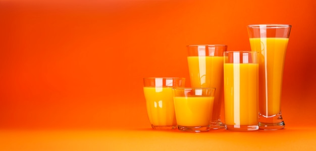 Glasses of orange juice on color orange background with copy space for text, fresh citrus cocktail