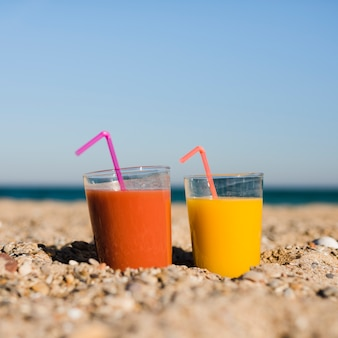 Glasses of orange and yellow juice with drinking straw on sand at beach against blue sky
