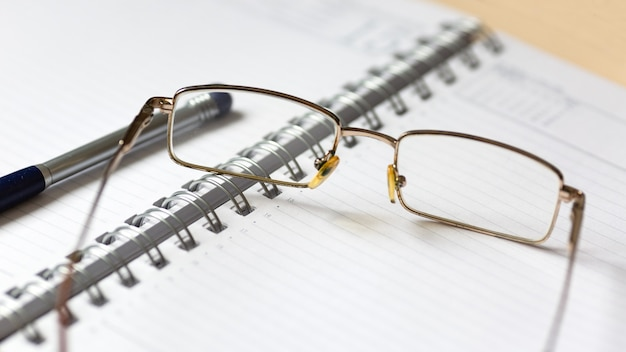 Glasses and a pen on an open notebook.