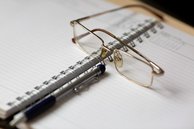 Glasses and a pen on an open notebook.,