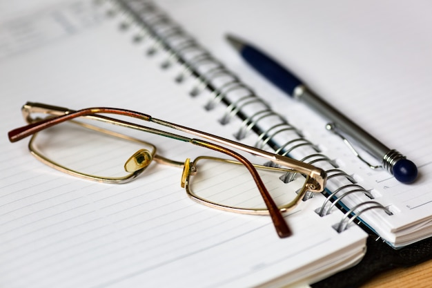 Glasses and a pen on an open notebook