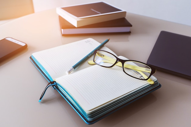 Glasses and a pencil on a notebook, a diary. business education