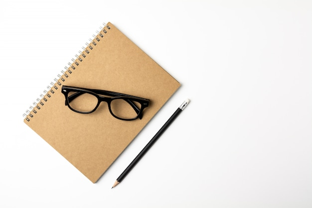 Glasses, pencil and a notebook on white background- for business concept background