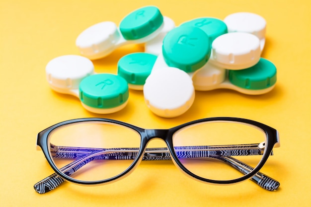 Glasses on the  of a pile of containers for storing contact lenses on yellow