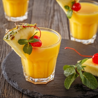 Glasses of pineapple juice with pieces of pineapple, cocktail cherry  and mint on wooden table.