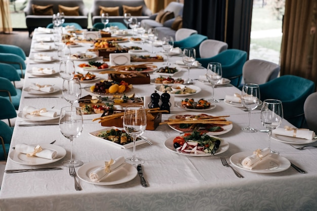 Glasses and plates on long table in restaurant for celebration