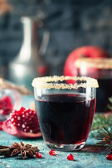 A glasses of pomegranate juice with fresh pomegranate fruits and fir tree branches on blue table