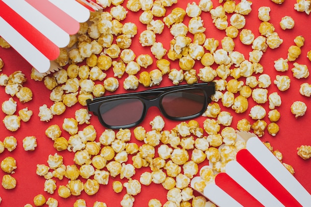 Glasses and popcorn on red top view