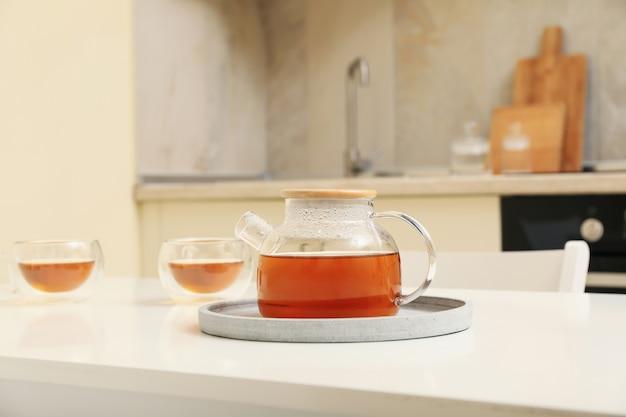 Glasses and pot of tea against kitchen interior