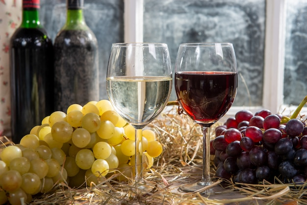 Glasses of red and white wine with grape