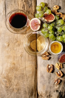 Glasses of red and white wine with grapes, figs, goat cheese and walnuts over old wooden background. flat lay, copy space