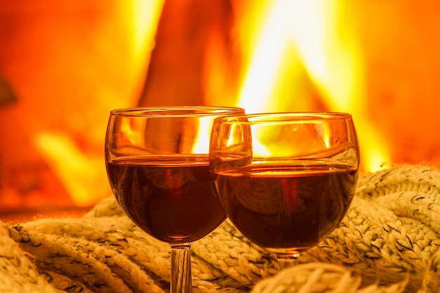 Glasses of red wine against cozy fireplace background, closeup, winter vacation.