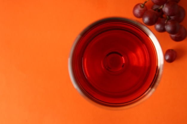 Glasses of red wine and grape on orange background