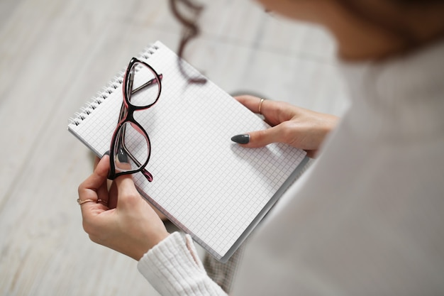 Glasses for sight and a notebook in the hands of a young girl.