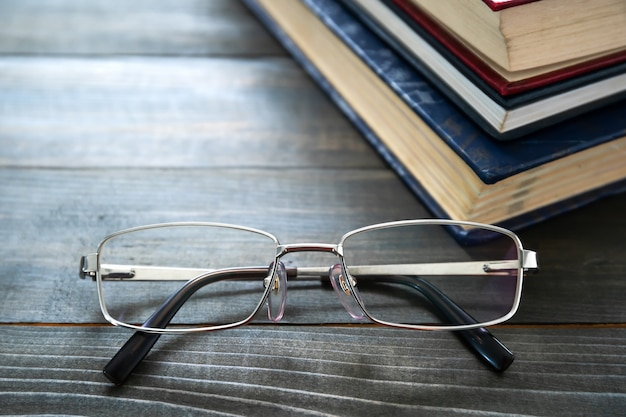 Glasses and stack of hardcover books over wooden table