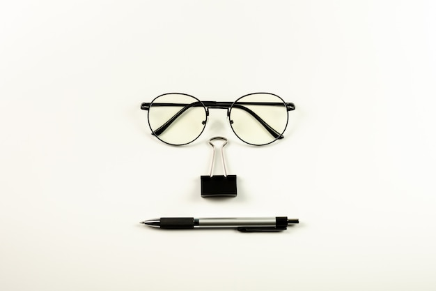 Glasses, stamp paper clip and pen on white background