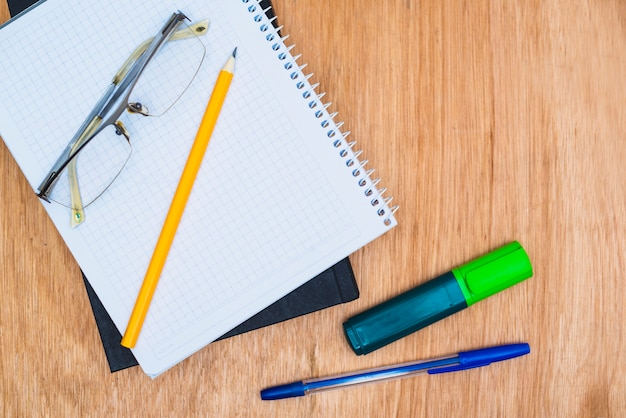Glasses on stationery and textbook