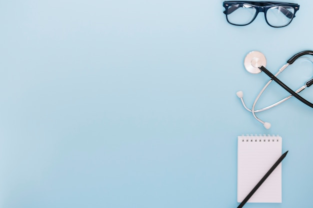 Glasses and stethoscope near notebook